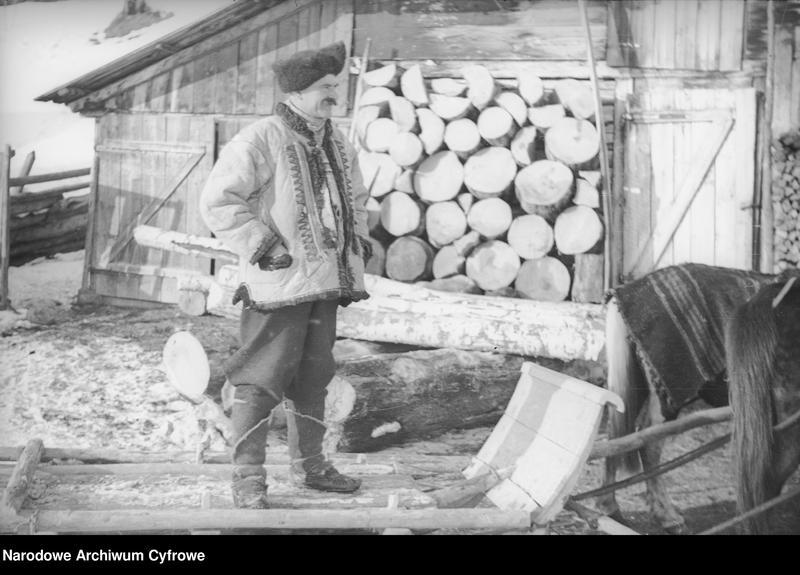 Obiekt Hucuł stojący przed drewnianą chatą przy saniach. z jednostki Huculskie typy ludowe