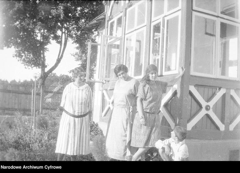 """Obraz z jednostki """"Fotografie rodzinne przed drewnianym domkiem"""""""