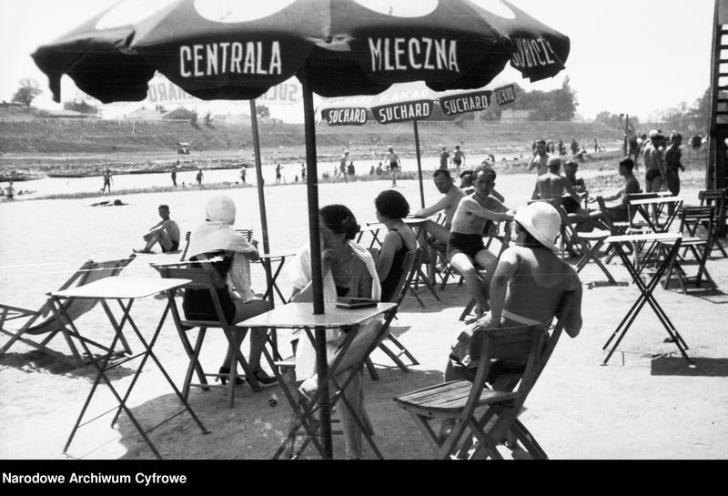 Obiekt Plażowicze podczas wypoczynku przy stolikach pod parasolami. z jednostki Plaża Towarzystwa Uniwersytetu Robotniczego w Krakowie