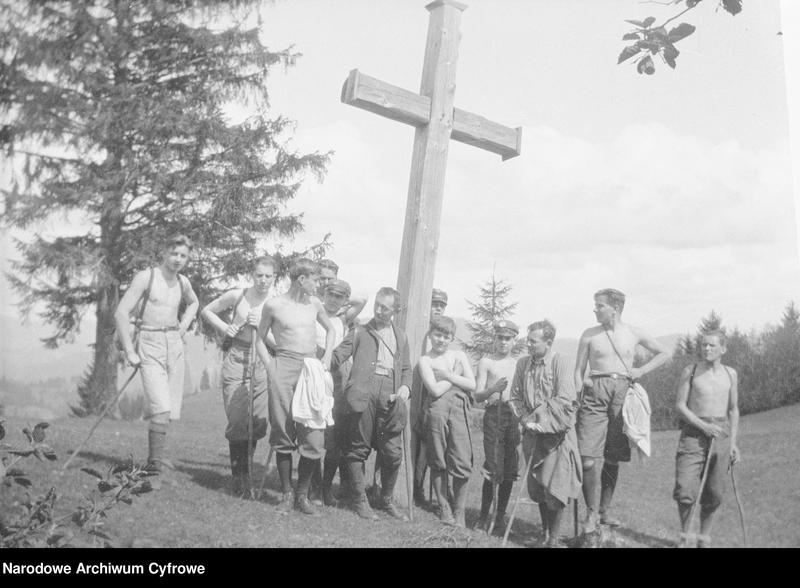 """Obraz z jednostki """"Grupa mężczyzn i chłopców pod krzyżem podczas wycieczki w górach"""""""